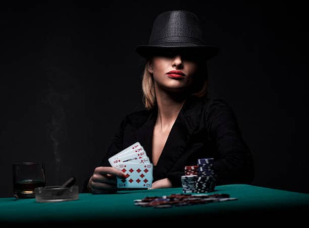 a woman with a hat holding poker cards