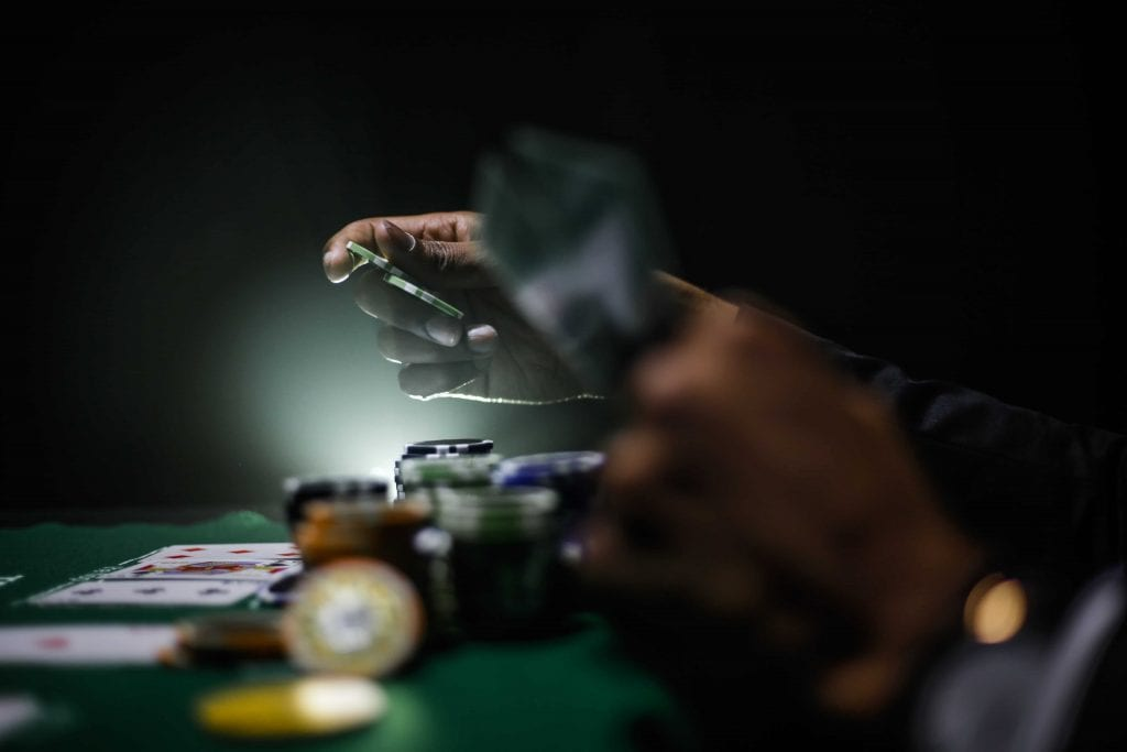 poker chips and poker cards held by a player