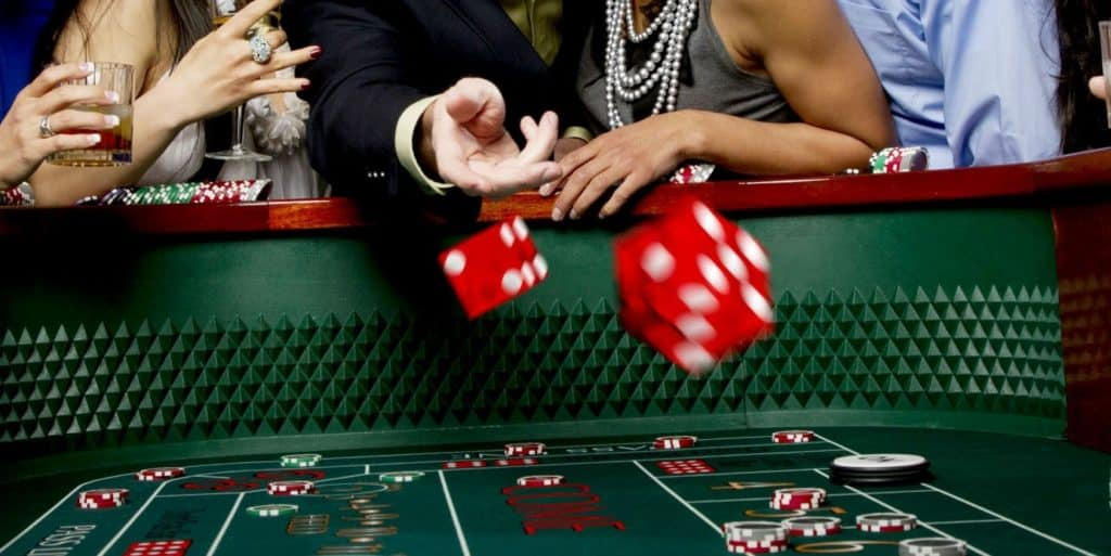 a man throwing red dices on a casino table